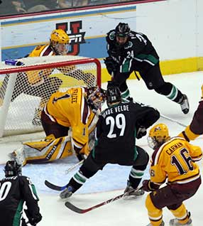 Chris Porter (24) wraps it around and in, past Minnesota goalie Jeff Frazee, to win and overtime and send North Dakota to the Frozen Four. (photo: Frank Mazzocco)