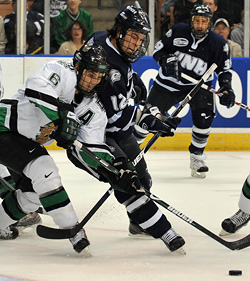 UNH\'s forward Bobby Butler battles North Dakota senior defenseman Zach Jones for control.