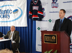 Robert Morris coach Derek Schooley speaks, as Atlantic Hockey commissioner Bob DeGregorio looks on.
