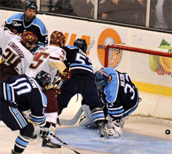 Matt Lombardi jams in the game winner past Maine goalie Dave Wilson, capping his hat trick and a Hockey East title. (photo: Josh Gibney)
