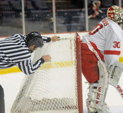A referee checks the net for a hole. There was none. New Hampshire\'s first goal went through the net, and was allowed after video review. (photo: Brad Pettengill)