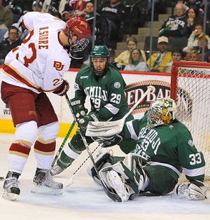 Denver\'s Nick Shore competes against Bemidji State goalie Dan Bakala and defenseman Brad Hunt during 2010-11. (photo: Scott Pierson)