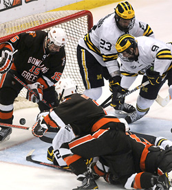Luke Moffatt (9) jams in the game winner off a scramble in the second overtime. (photo: Adam Glanzman/Michigan Daily)