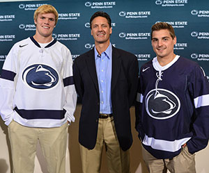 Penn State coach Guy Gadowsky (middle) helps show off his nascent program\'s new uniforms.