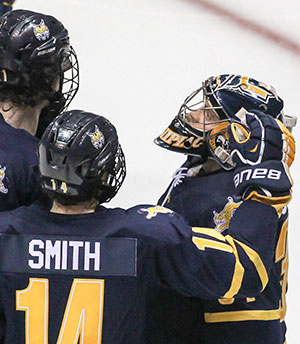 Quinnipiac goalie Michael Garteig is consoled by teammates after a 3-2 double overtime loss to Colgate in the ECAC semis. (photo: Robert Dungan)